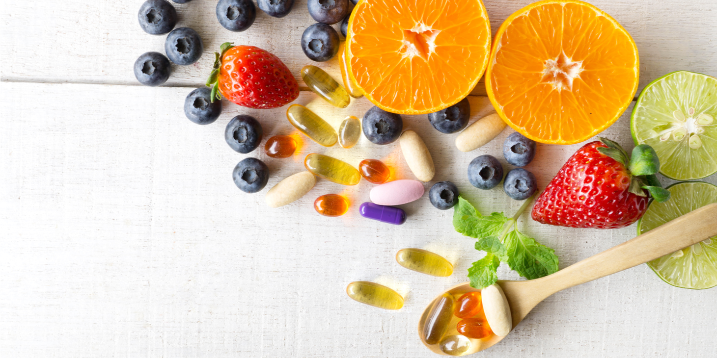 A wooden spoon holding a variety of multivitamin pills among a backdrop of fruits