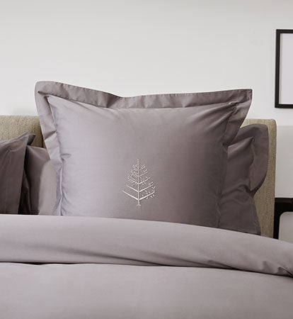 Bedding Collection items on made bed with lamp and plant decoration on sides on stands