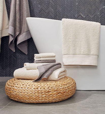 Towel Collection main, bathrrom with towel set on stand, bath tub with bath towel, sink with towels sets underneath