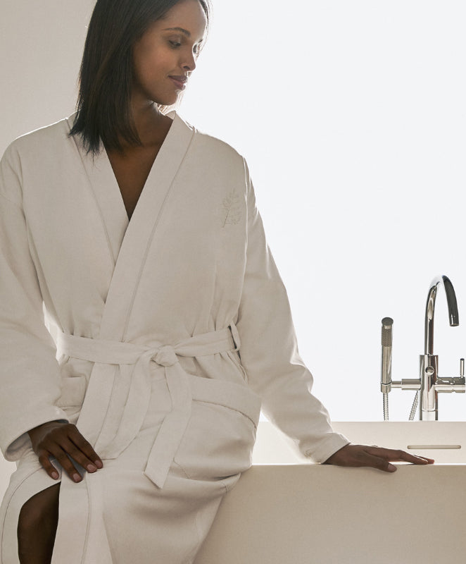 Robe Collection main, woman in robe sitting on bath tub