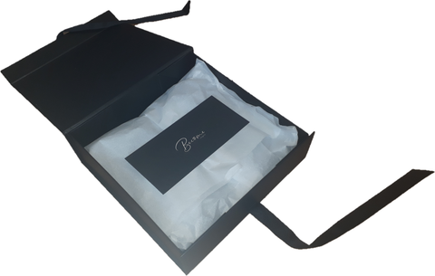 open gift box showing product wrapped in tissue paper topped with a branded logo leaflet