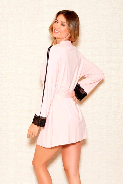 Back side view of woman modelling pink dressing gown with black stripe on shoulders