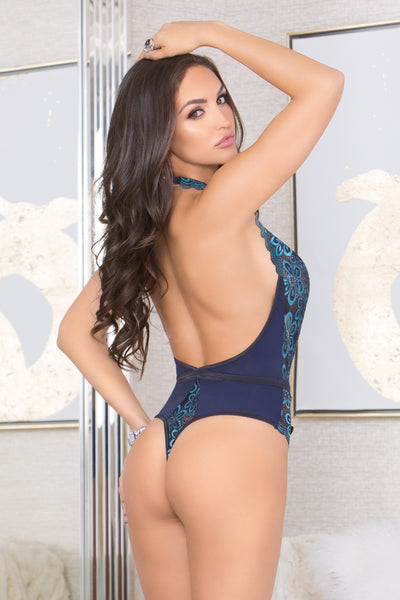 Back view of a woman holding her hair wearing a thong bodysuit that looks like a swimsuit