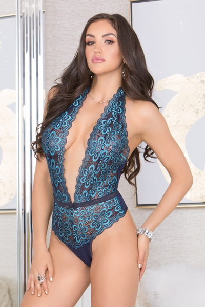woman posing proud like a peacock wearing a blue haterneck low plunge bodysuit teddy