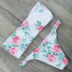 This bandeau bikini set is white and decorated with pink flowers and green leaf patterns. It allows you to choose if you want it shaped like a bandeau or with a knot in the front of the top part of the bikini. The top is wire-free with removable pads. The bottom is a low waist design and very comfortable. The set is made of nylon and spandex.