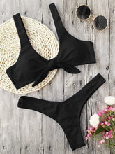 This black bikini set has a low waist bottom and the top part has shoulder bands and is knotted in the front. The top part also gives a nice push-up and it's completely wire free. The set is made of 82% polyester and 18% spandex, which gives the bikini flexibility and makes it shape beautifully around your body.