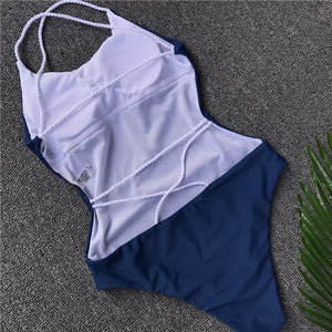 This beautiful and trendy dark blue swimsuit is padded and has an open back, the white bands in the back give it a nice touch as they cross from side to side and helps the swimsuit highlight your bodylines. The material is solid and made of 82% nylon and 18% spandex.