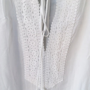 This is a traditional yet trendy white cover-up tunica, it's perfect to put over your swimwear and it provides a high level of comfort and will make you look great.  Its arm length is three quarters long and the collar section is wide and shaped like a V, the width can be adjusted with a long lace with frilling at each end. The collar and is decorated with a beautiful floral embroidered pattern. This beautiful tunica is made out of cotton.