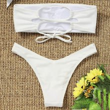 This is a white bandeau bikini set. The top has removable pads and elastic bands in the back to easily adapt the fitting for your body. The bottom has a low waist design and very comfortable. The set is made of nylon and spandex.