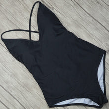 This black swimming suit is padded and has a deep cut in the back, the elastic bands in the back help to adapt the swimsuit to fit your body perfectly.  The material is nylon, polyester, acetate, and spandex.