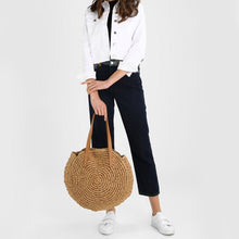 This modern brown shoulder bag's exterior has a retro paper circular design and is made out of hard straws and the lining material inside is polyester. It has multiple pockets, including a cell phone pocket. It has two shoulder straps that are 23cm / 9in to the top.