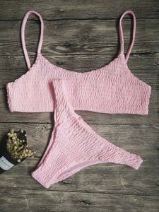 Trendy pink bandeau bikini set with decorative smock, made of polyester and cotton.