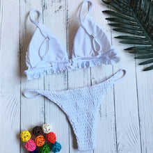 Trendy white triangular bikini set with frilling. This set has decorative smock and is made of polyester and cotton.