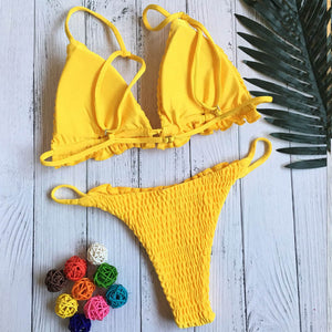 Trendy yellow triangular bikini set with frilling. This set has decorative smock and is made of polyester and cotton.