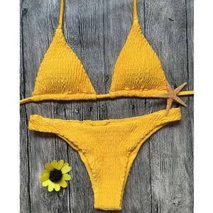 Trendy yellow triangular bikini set. This set has decorative smock and is made of polyester and cotton.