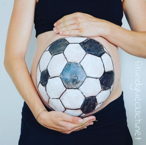 pregnant belly painted as soccer ball
