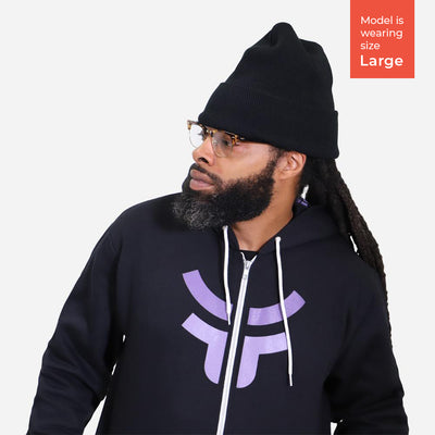 man with beard looking away while wearing black fearless zip up hoodie and beanie