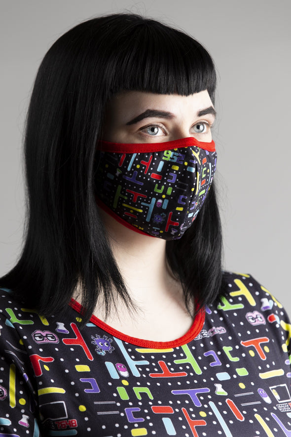 Model wearing 8-Bit Baby Face Mask and Onesie. Matching red trim, black background, and video game iconography.