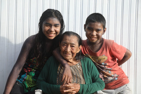 Three Yawanawa tribe members, a grandmother and her granddaughter and grandson, are smiling and embracing.