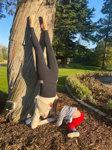 Alex Eagle doing hand stands next to a tree.