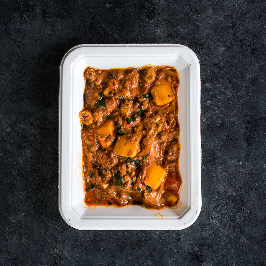 The Butternut Cocoa Chili from paleo meal delivery company, Balanced Bites Meals, is rich, flavorful, and super comforting. The dish pictured here is paired with sour cream, avocado slices, lime wedges, and cilantro.