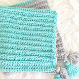 crochet handmade baby blanket in aqua and grey with corner tassels from Design by AW