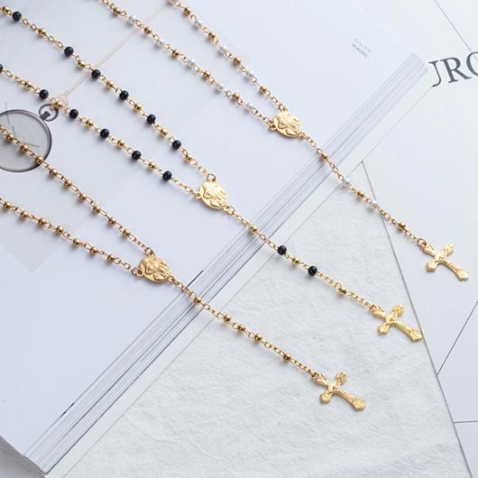 Timea Rosarys with different coloured pearls and golden cross pendant on bible