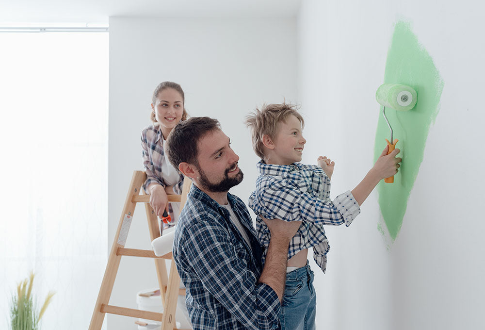 A father holding up a child to paint with a paint roller on the wall.