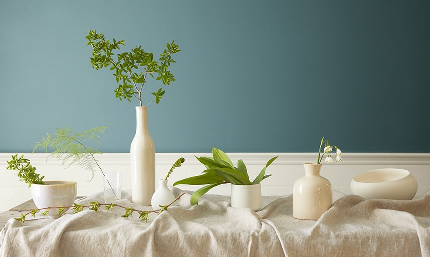 Benjamin Moore's Color of the Year 2136-40 Aegean Teal in  dining area with white trim, and beige table cloth and vases