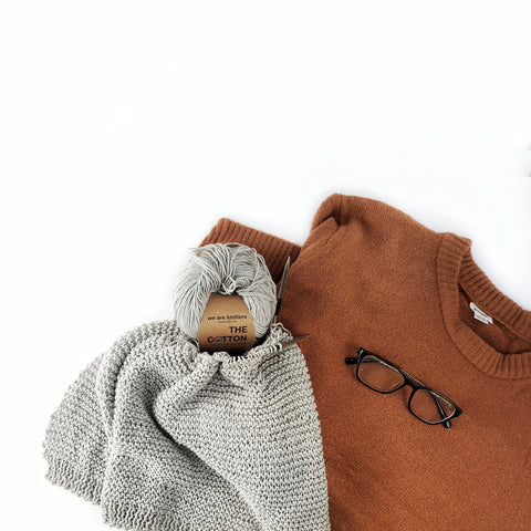 Garter stitch knitwear beside orange sweater and glasses