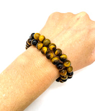 Load image into Gallery viewer, Tiger's Eye is a brown marbleized stone that offers protection to the wearer and is most associated with the solar plexus chakra. Bracelet materials include 8mm tigers eye stones on an elastic cord. Two bracelets included in this set. Custom sizing is available by Contacting Us.
