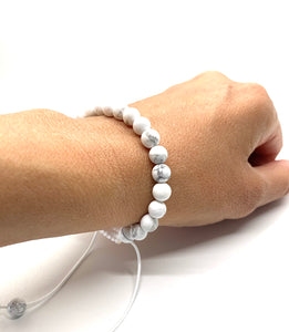 Howlite is a white marbleized stone that promotes awareness and is most associated with the crown chakra. Bracelet materials include 6mm howlite stones on an adjustable string that measures 6-9 inches to fit men, women & children. One size fits most.