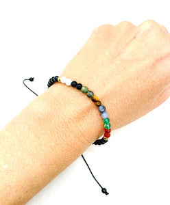 Ignite all your chakras with this rainbow macrame bracelet! Bracelet materials include 4mm onyx stones on an adjustable string that measures 6-9 inches to fit men, women & children. One size fits most.