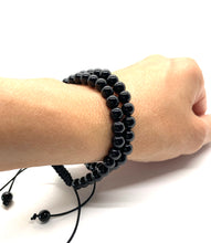 Load image into Gallery viewer, Onyx is a shiny black stone that inspires one to step into their personal power and is most associated with the root chakra. Bracelet materials include 6mm onyx stones on adjustable string that measures 6-9 inches to fit men, women & children. Two bracelets come in this set. One size fits most.
