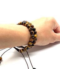Load image into Gallery viewer, Tiger's Eye is a brown marbleized stone that offers protection to the wearer and is most associated with the solar plexus chakra. Bracelet materials include 6mm tiger's eye stones on adjustable string that measures 6-9 inches to fit men, women & children. Two bracelets come in this set. One size fits most.