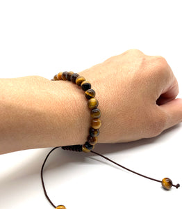 Tiger's Eye is a brown marbleized stone that offers protection to the wearer and is most associated with the solar plexus chakra. Bracelet materials include 6mm tiger's eye stones on an adjustable string that measures 6-9 inches to fit men, women & children. One size fits most.