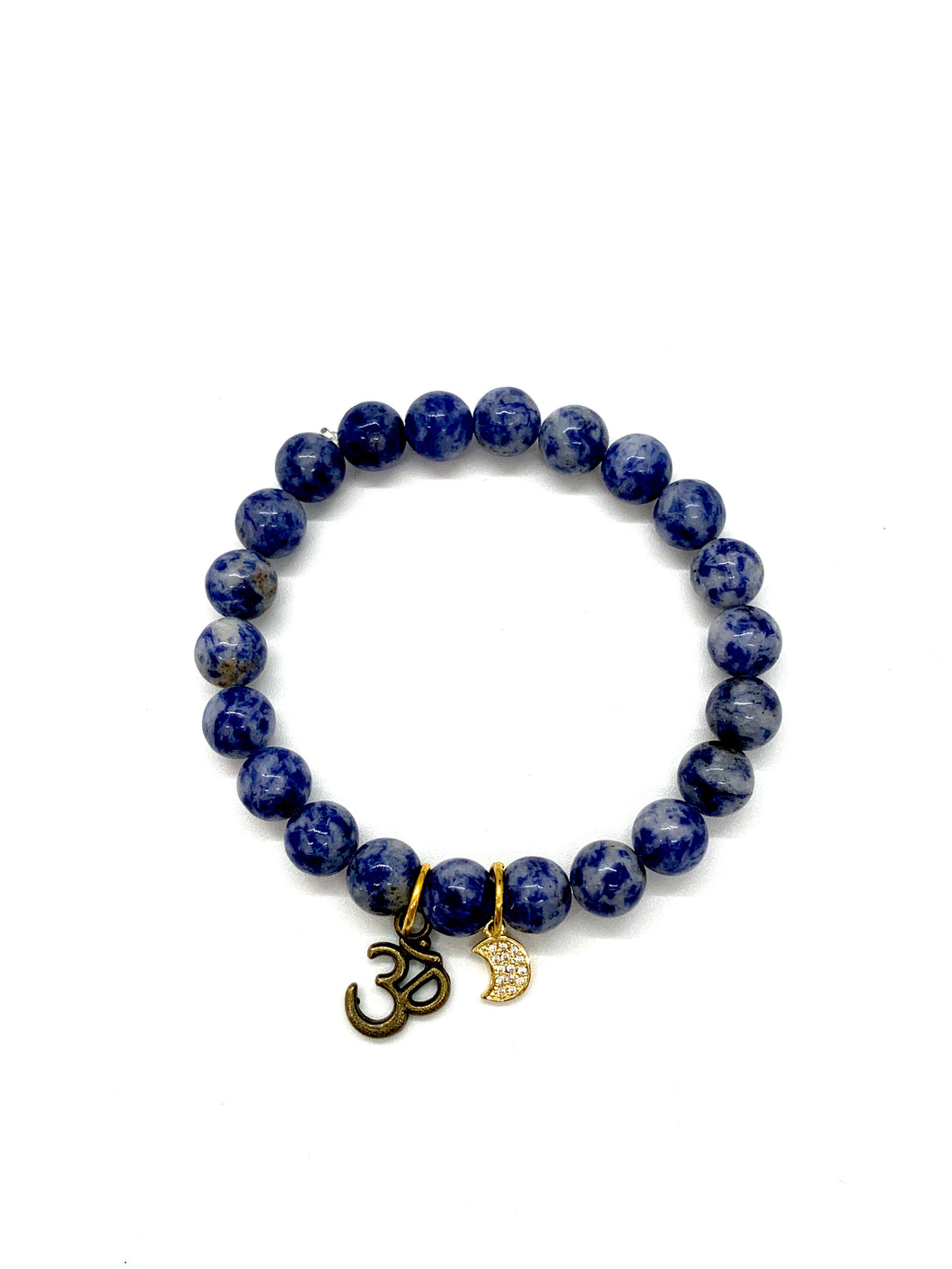 The OM symbol is for high vibration and the moon is for action. Bracelet materials include 8mm sodalite stones on an elastic cord with a bronze Om charm and an 18k gold-plated moon charm. Both are adorned with Austrian crystals. Bracelet measures 7.25 inches. Charms are lead & nickel free. Custom sizing is available by Contacting Us.