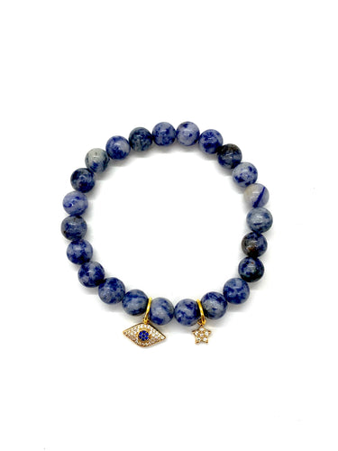 The evil eye wards off negativity offering protection to the wearer and the star promotes encouragement. Bracelet materials include 8mm sodalite stones on an elastic cord with an 18k gold-plated eye charm and an 18k gold-plated star charm. Both charms are adorned with Austrian crystals. Bracelet measures 7.25 inches. Charms are lead & nickel free. Custom sizing is available by Contacting Us.