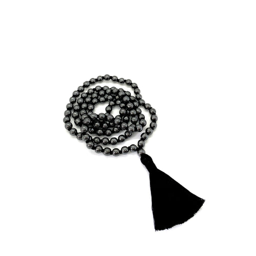 Materials include 108, 6mm hematite stones that are hand knotted on a black cotton string w/ a two-inch black cotton tassel