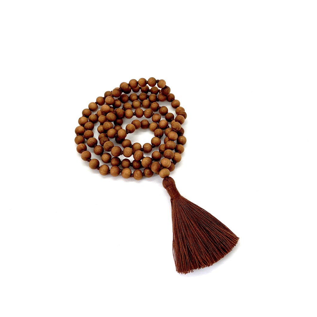 Materials include 108, 6mm sandalwood beads that are hand knotted on a brown cotton string w/ a two-inch brown cotton tassel for earthing energy