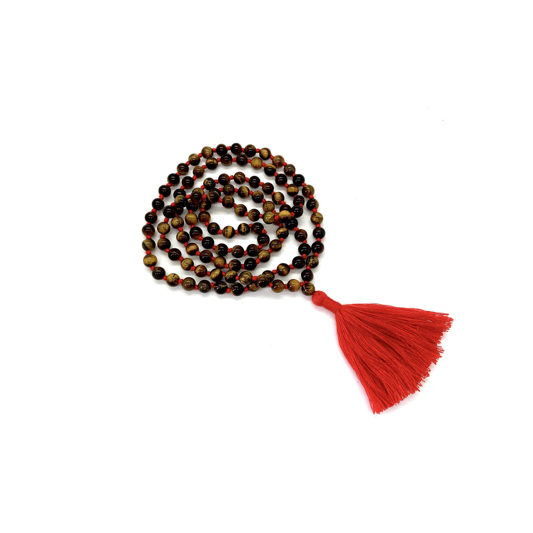 Materials include 108, 6mm tiger's eye stones that are hand knotted on a red cotton string w/ a two-inch red cotton tassel for root chakra energy