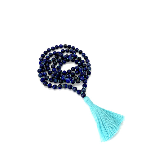 Materials include 108, 6mm lapis lazuli stones that are hand knotted on a turquoise cotton string w/ a two-inch turquoise cotton tassel
