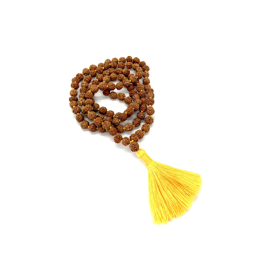 Rudraksha is a brown seed bead that promotes tranquility & concentration. Materials include 108, 7mm rudraksha beads that are hand knotted on a yellow cotton string with a two-inch yellow cotton tassel for solar plexus energy. This mala is unisex and will likely wrap four times around the wrist for women & three for men. If worn as a necklace, it measures 36 inches.