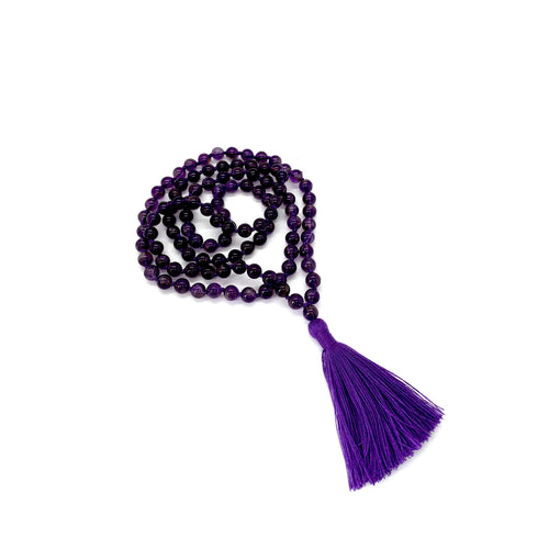 Materials include 108, 6mm purple amethyst stones that are hand knotted on a purple cotton string w/ a two-inch purple cotton tassel