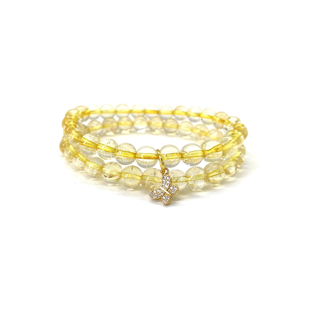 Bracelet materials include 8mm citrine stones on an elastic cord w/ an 18k gold-plated butterfly charm that is adorned w/ Austrian crystals