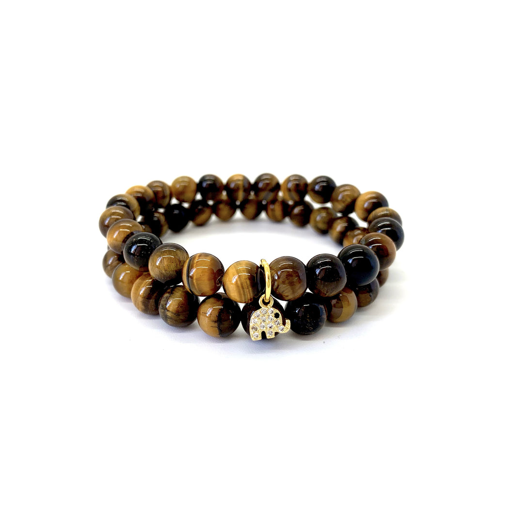Bracelet materials include 8mm tiger's eye stones on an elastic cord w/ an 18k gold-plated elephant charm that is adorned w/ Austrian crystals