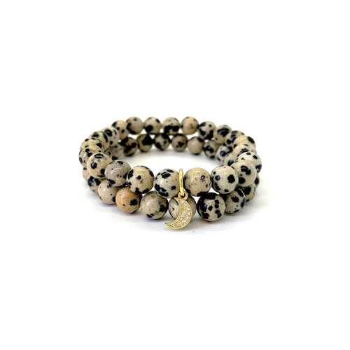 Bracelet materials include 8mm dalmatian jasper stones on an elastic cord w/ an 18k gold-plated moon charm that is adorned w/ Austrian crystals