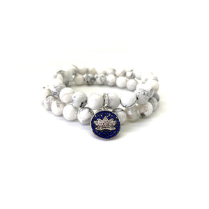 Bracelet materials include 8mm howlite stones on an elastic cord w/ a silver-plated lotus charm that is adorned w/ Austrian crystals