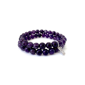 Bracelet materials include 8mm amethyst stones on an elastic cord w/ a silver-plated script love charm that is adorned w/ Austrian crystals
