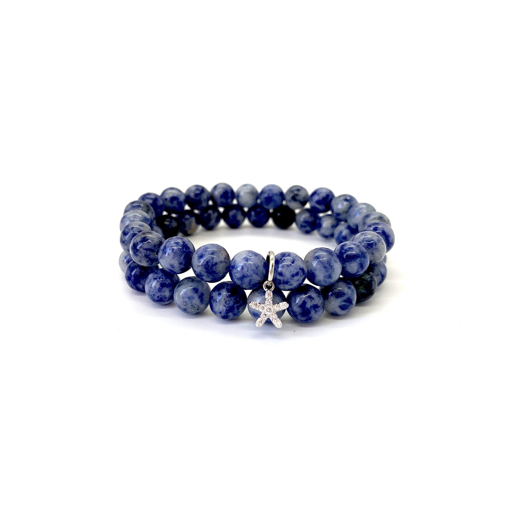 A starfish represents love and resiliency. Bracelet materials include 8mm sodalite stones on an elastic cord with a silver-plated starfish charm that is adorned with Austrian crystals. Both bracelets measure 7.25 inches. Charm is lead & nickel free. Custom sizing is available by Contacting Us.